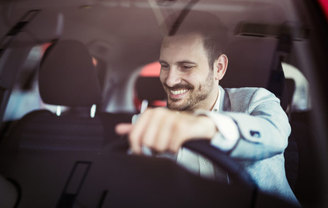 Attractive happy young man driving car and smiling