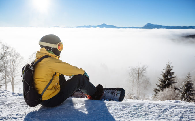 Snowboarder sitting and looking at mountain chain