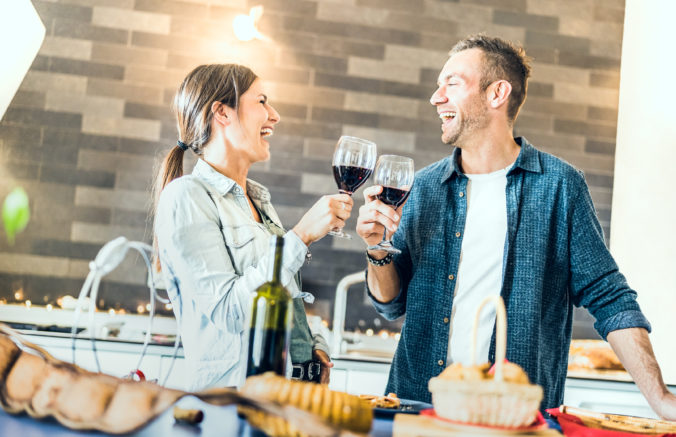 Young couple in love drinking red wine at house kitchen - Happy millenial people at home enjoying aperitif time cheering together at jubilee anniversary - Genuine youth concept on bright indoor filter