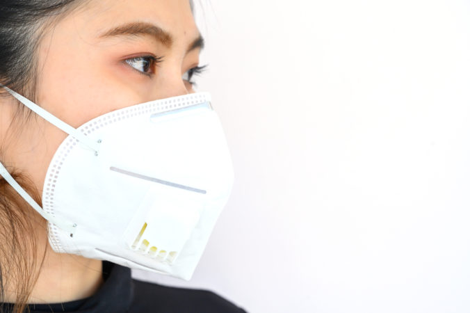 Close up of young Asian woman wearing N95 mask for protect smog PM2.5 bad air pollution.