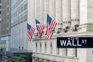 Wall street sign in New York City with New York Stock Exchange background.