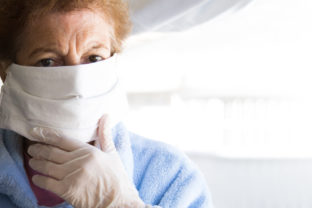 Senior woman using mobile phone with mask and disposable medical gloves. Safety measures during the coronavirus outbreak