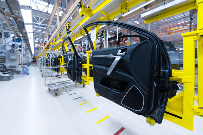 Preparation for installation of body part in car factory. door from car on production line