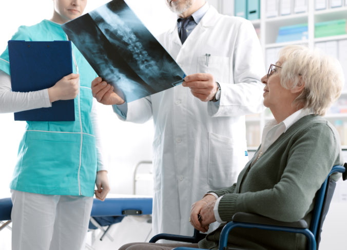 Doctor checking a senior female patient's x ray image during a visit at the hospital, injury and osteoporosis concept