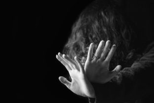 Violence against women. Black and white portrait of scared and desperate woman, focus on the hands in protective gesture