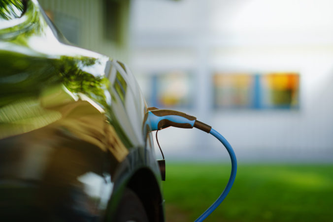 Electric Car is charging in front of house