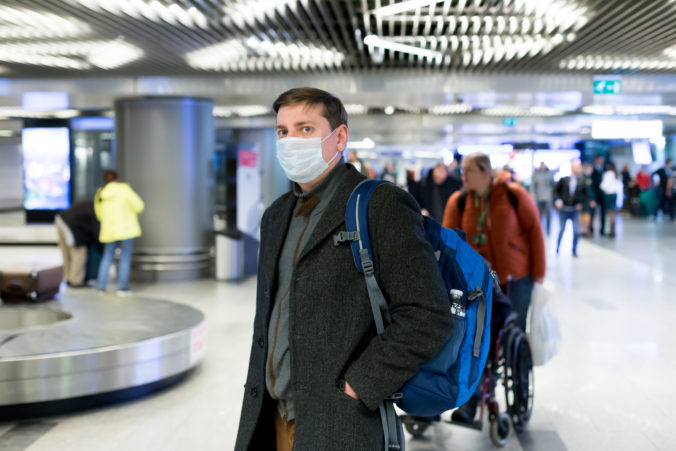 Young European man in gray coat, protective disposable medical mask in airport. Afraid of dangerous N CoV 2019 influenza coronavirus mutated and spreading in China. Blue backpack, suitcase on wheels