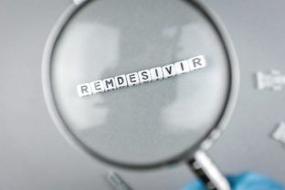 Magnifying glass on alphabet dices with the word Remdesivir a possible treatment for Corona Virus