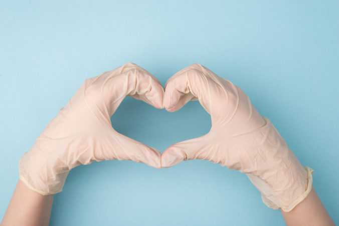 Save life concept. Cropped top above overhead close up photo of hands making giving shape of heart with fingers isolated over blue background