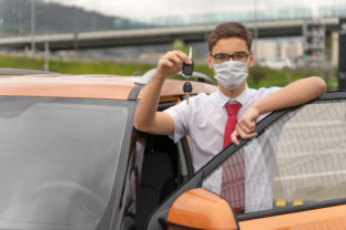 Concept of a personal driver service. Chauffeur drive. Personal chauffeur in a protective face mask
