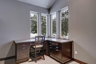 Gray and blue home office features a vaulted ceiling