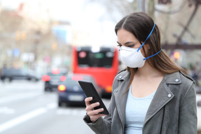 Woman with mask using phone with city traffic background