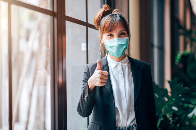 Asian Business Woman Standing and Showing Thumbs up in Working Office. She Wearing Virus Protective Mask in Prevention for Coronavirus or Covid 19 Outbreak Situation - Healthcare and Business Concept