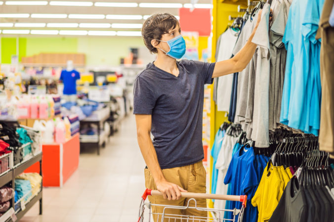 Man in a clothing store in a medical mask because of a coronovirus. Quarantine is over, now you can go to the clothing store