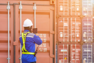 Foreman control loading Containers box from Cargo freight ship by tablet,Freight shipping containers at the docks,Large container shipping at shipping yard main transportation of cargo container.