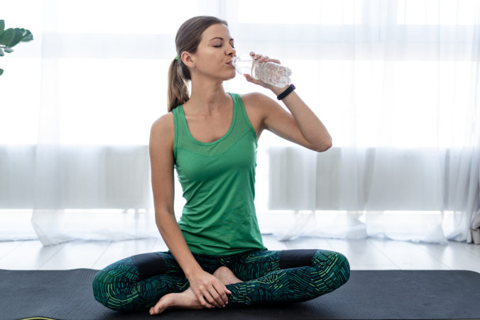 Young sporty woman drinking water from plastic bottle