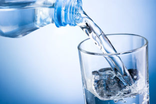 Closeup of bottle of water pouring into a glass
