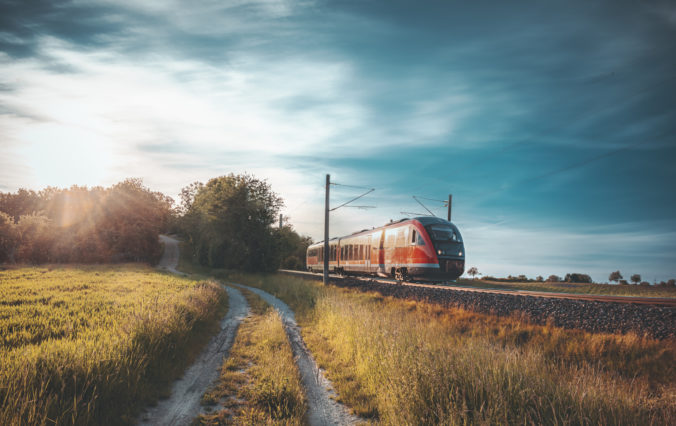Red German train traveling on railway tracks through nature