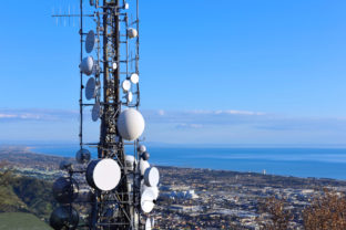Aerial view of a telecommunication tower, satellite dish, network repeaters, base transceiver. Antenna for wireless network. Cellular station for smart city connect and coastline as background.