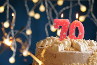 Birthday cake with 70 number pink candles and burning sparkler on blue backgraund. Close up