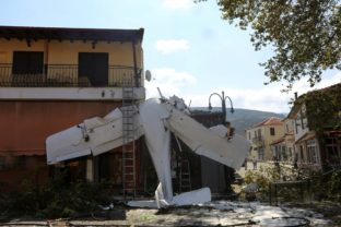 A small plane lays on a building after a crash in the village of Proti, near Serres town, northern Greece, on Monday, Aug. 3, 2020. The single-engine plane crashed on Monday morning into the front of a small building but no injuries were reported and the pilot of the Cessna aircraft is well.