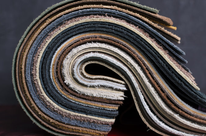 Closeup of rolled samples of upholstery leather against dark background