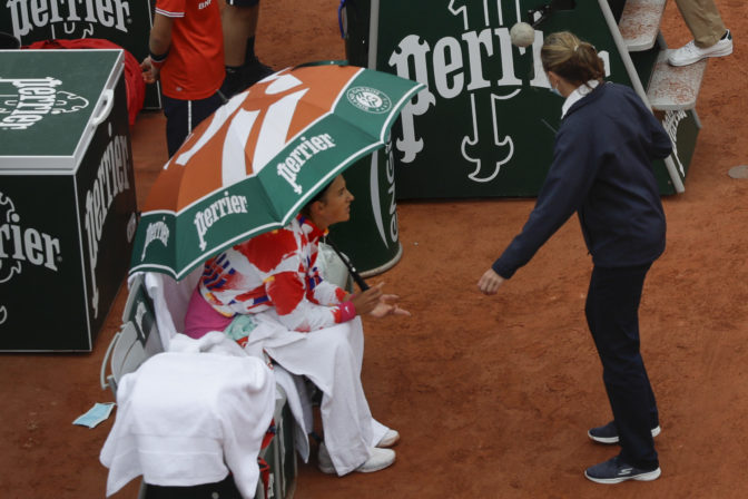 Victoria Azarenka of Belarus complains about the weather conditions and ask the umpire to suspend the first round match of the French Open tennis tournament against Montenegro's Danka Kovinic at the Roland Garros stadium in Paris.