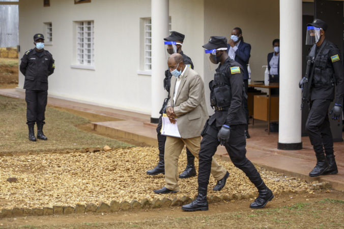 """Paul Rusesabagina, center, whose story inspired the film """"Hotel Rwanda"""", is led out in handcuffs from the Kicukiro Primary Court in the capital Kigali, Rwanda Monday, Sept. 14, 2020. A Rwandan court on Monday charged Paul Rusesabagina with terrorism, complicity in murder, and forming an armed rebel group, while Rusesabagina declined to respond to all 13 charges, saying some did not qualify as criminal offenses and saying that he denied the accusations when he was questioned by Rwandan investigators."""