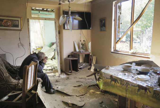 Yury Melkonyan, 64, sits in his house damaged by shelling from Azerbaijan's artillery during a military conflict in Shosh village outside Stepanakert, the separatist region of Nagorno-Karabakh, Saturday, Oct. 17, 2020. The latest outburst of fighting between Azerbaijani and Armenian forces began Sept. 27 and marked the biggest escalation of the decades-old conflict over Nagorno-Karabakh. The region lies in Azerbaijan but has been under control of ethnic Armenian forces backed by Armenia since the end of a separatist war in 1994. ()