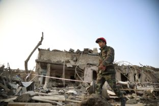 A soldier walks past a destroyed house in a residential area that was hit by rocket fire overnight by Armenian forces, early Saturday, Oct. 17, 2020, in Ganja, Azerbaijan's second largest city, near the border with Armenia. Azerbaijan has accused Armenia of striking its second-largest city with a ballistic missile that killed at least 13 civilians and wounded 50 others in a new escalation of their conflict over Nagorno-Karabakh.