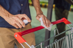 Man hand disinfecting shopping cart with alcohol spray for corona virus or Covid 19 protection