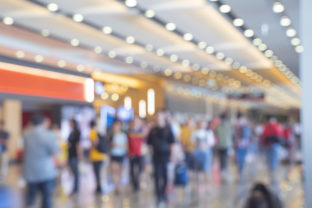 Blurred,defocused background of Crowd in trade event exhibition hall. Business trade show,shopping mall and marketing advertisement concept,MICE industry business concept