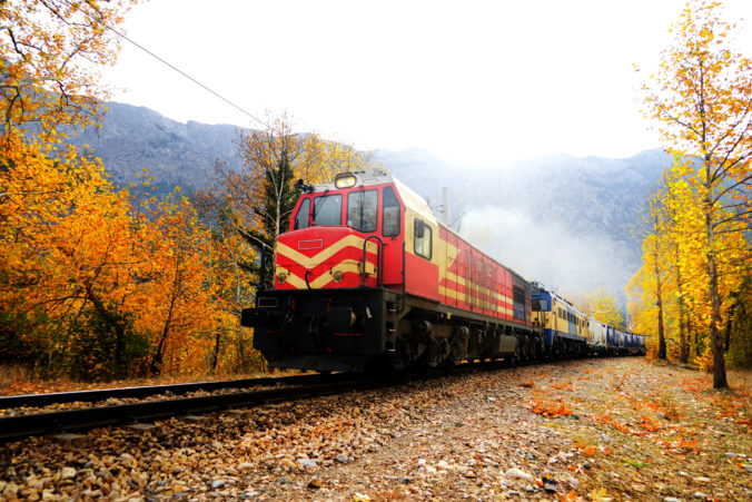 Passenger Train in countryside landscape with colorful autumn leaves and trees