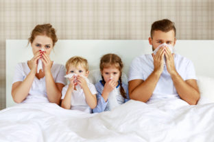 Colds and viral diseases. family with runny nose and fever in bed