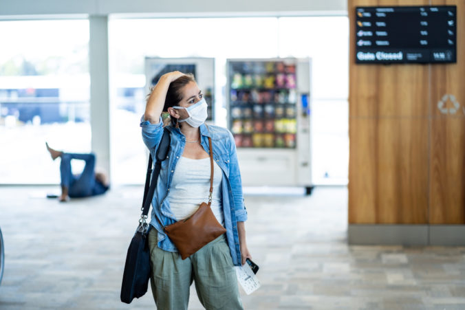 COVID 19 worldwide borders closures.Traveler with face mask stuck in airport terminal after being denied entry to other countries. Passenger stranded in airport on his travel back to home country.