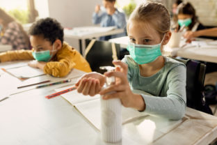 Elementary student wearing protective face mask and disinfecting her hands in the classroom.