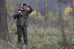 Man in camouflage and with guns in a forest belt on a spring hun