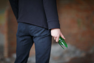 A broken beer bottle in the man's hand used as a weapon
