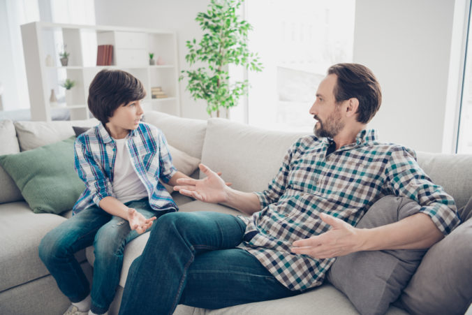 Portrait of two nice attractive friendly guys dad and pre teen son sitting on couch discussing psychology generation problems in light white modern style interior living room