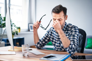 Frustrated, overworked freelancer working from home office
