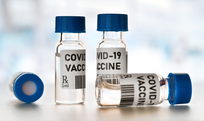 Coronavirus Covid 19 vaccine concept - small glass vials with blue caps on white table, closeup detail (own design - dummy bar code)