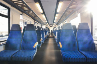 German train interior with two rows of empty seats and sunlight