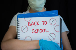 Close up of student wearing face mask and surgical gloves, holding school books with Back to School written on cover