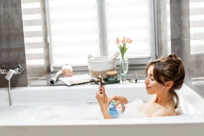 Young woman taking a bath, lying with a smart phone in bathtub with foam and rubber duck in the bathroom at home