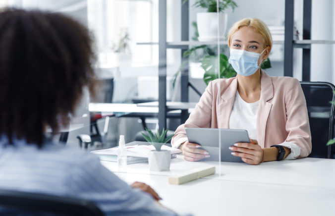 New normal and modern interview during covid 19 outbreak. HR manager with laptop looks at african american woman through protective glass