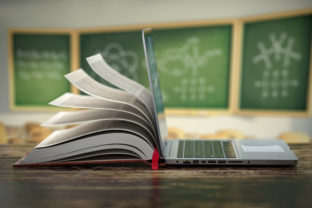 E learning online education or internet  encyclopedia concept. Open laptop and book compilation in a classroom.