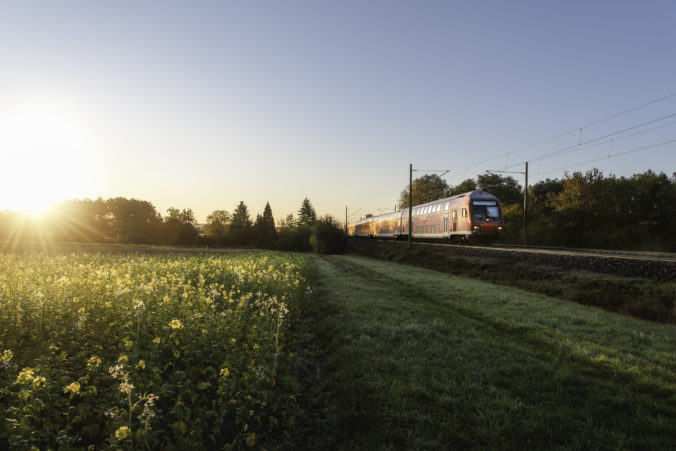 Red train and spring landscape at sunrise. Spring travel context