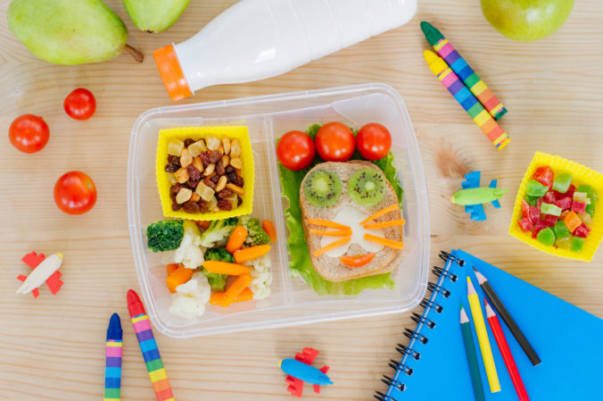 Plastic lunch box on a wooden table with school accessories
