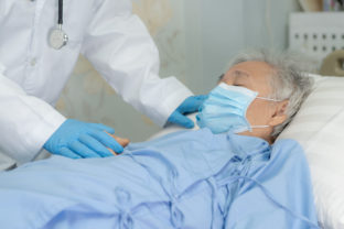 Doctor help Asian senior or elderly old lady woman patient wearing a face mask in hospital for protect safety infection and kill Novel Coronavirus (2019 nCoV) Covid 19 virus.