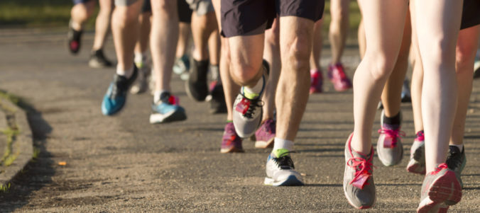 Legs of runners on a dirt path next to a lake